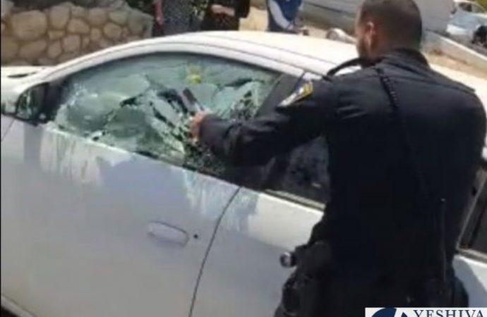 El policía destroza la ventanilla del automóvil para sacar al niño del interior