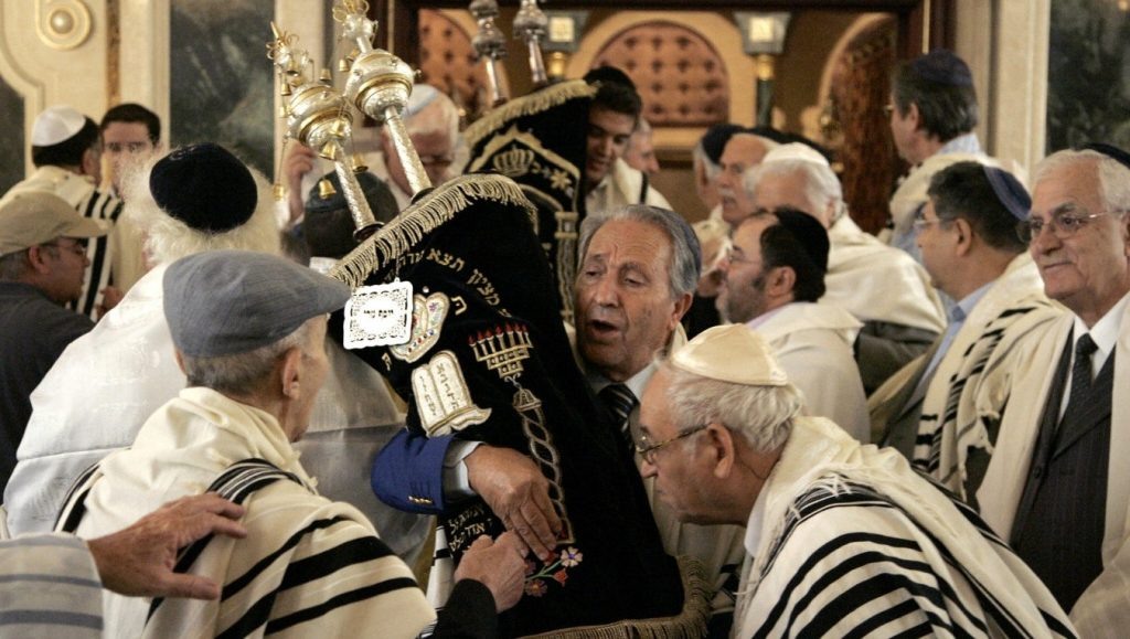 Miembros de la comunidad judía de Marruecos besan rollos de Torá en Simjat Torá en la Gran Sinagoga de Casablanca, Marruecos, el 5 de octubre de 2007. (Abdelhak Senna / AFP a través de Getty Images)